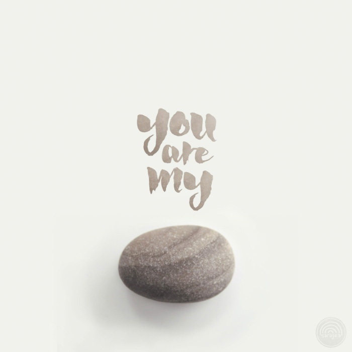 "Photograph of a smooth, grey-brown stone. The words ""you are my rock"" are written above it in matching grey-brown"